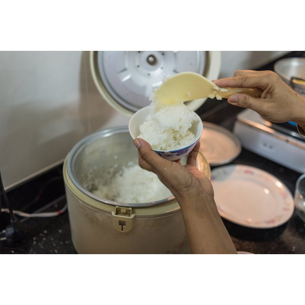 A close-up of a woman's hands serving up white rice from a rice cooker.