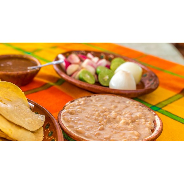 A bowl of refried beans on a restaurant table.