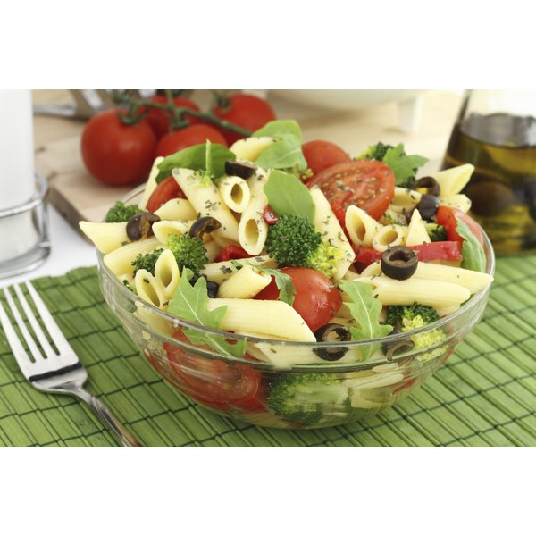 A bowl of fresh Italian pasta salad on a placemat.