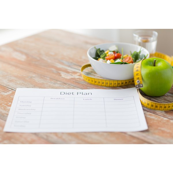 A diet plan on a table with a measuring tape, salad and an apple.