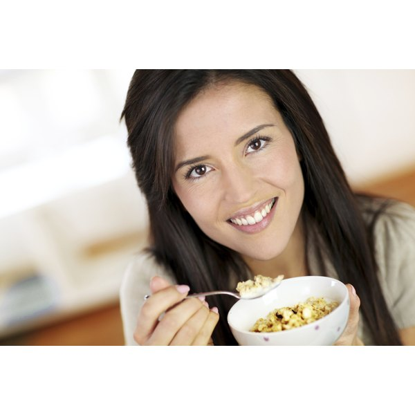 A woman enjoys her fiber one cereal for breakfast.