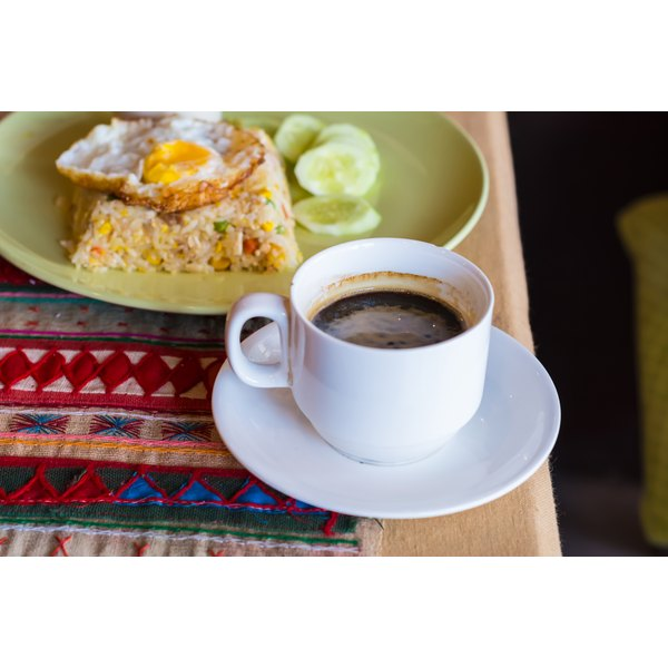An egg over fried rice and a cup of coffee on a breakfast table.