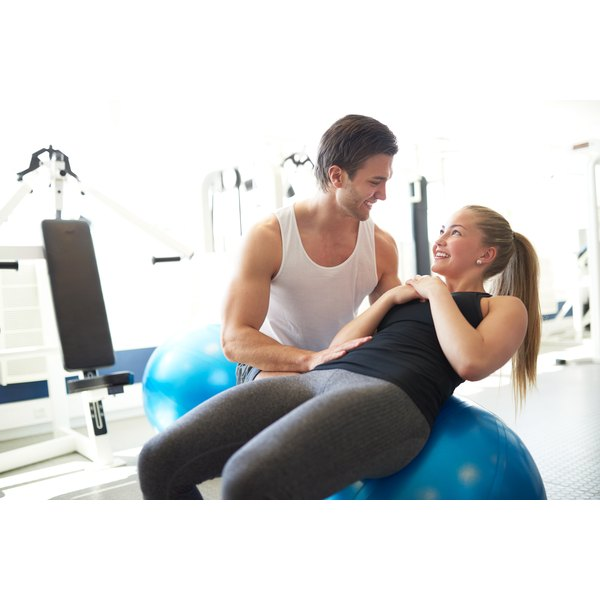 A trainer works with a women doing pilates.