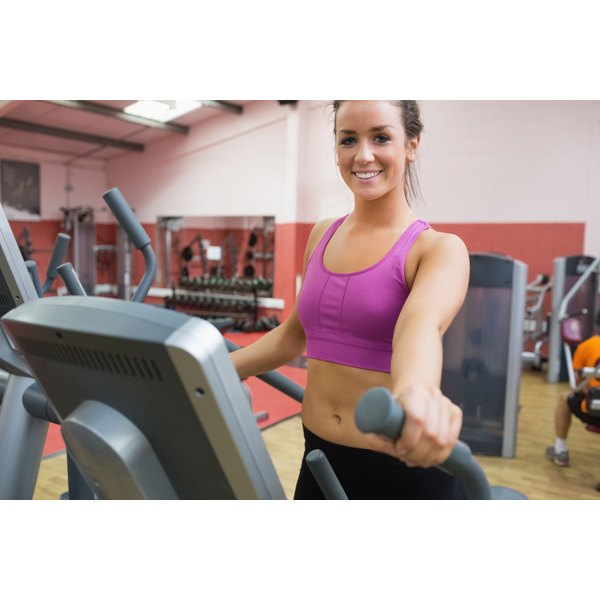 A young woman is using the elliptical machine.