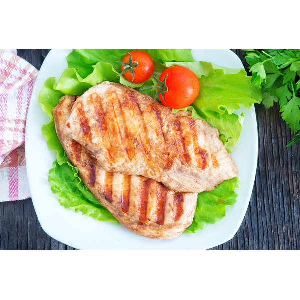 Two grilled chicken breasts on a plate.