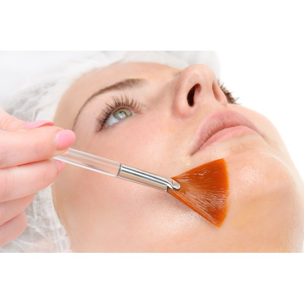 A woman is getting a facial peel applied.