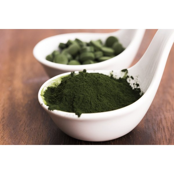 Spoonfuls of chlorella powder and supplements on a table.