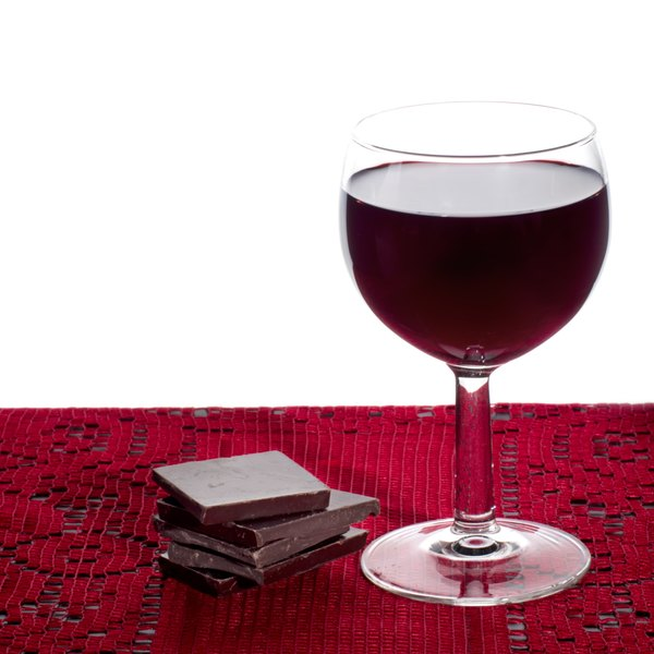 Close up of dark chocolate with a glass of red wine