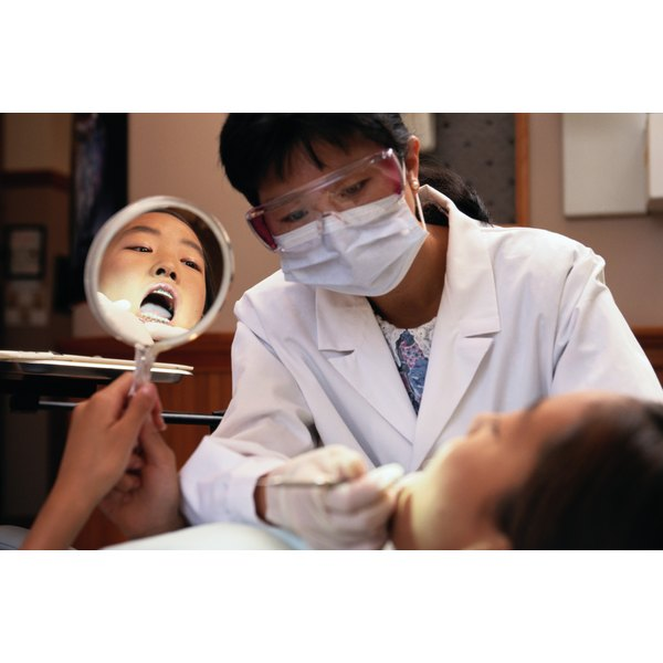 A dentist inspects a patient's mouth while patient holds a mirror to himself.