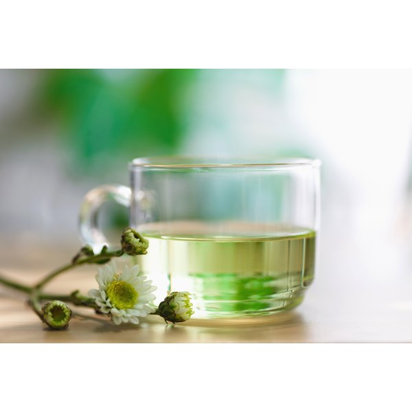 A glass of white tea and a flower clipping on a table.