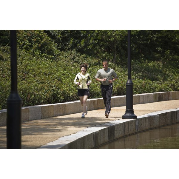 A man and woman are jogging on a trail.