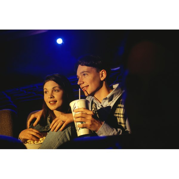 A teenage couple drinking a soda and eating popcorn.