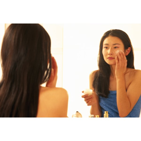 Woman looking in the mirror applying face cream