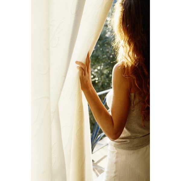 Woman looking out window, moving curtain aside.