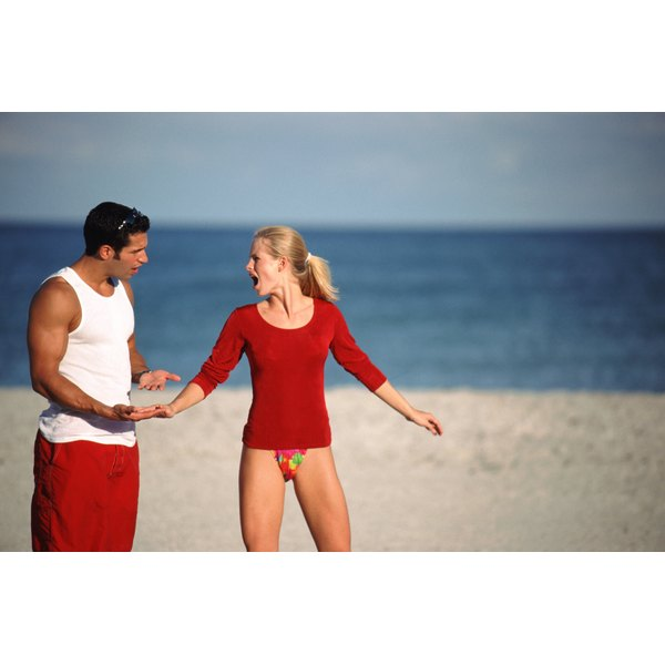 A young couple on the beach argue.