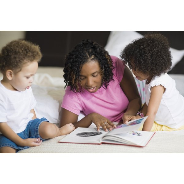 A woman reading a book to two toddlers.