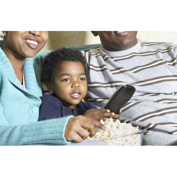 A family is watching a movie and eating popcorn.