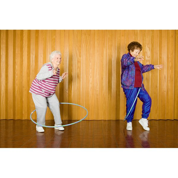 Elderly women using hula hoops.