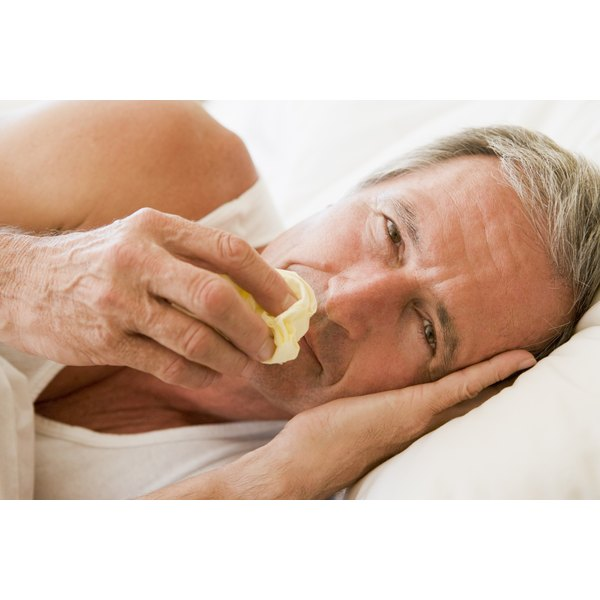 Sick man in bed with a tissue in hand