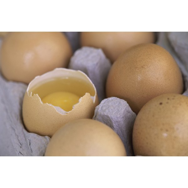 A cracked egg in an egg carton.