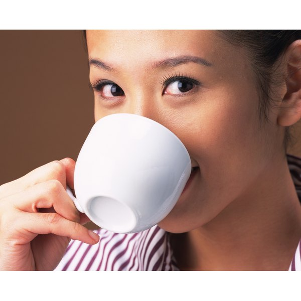 A woman is drinking from a coffee mug.