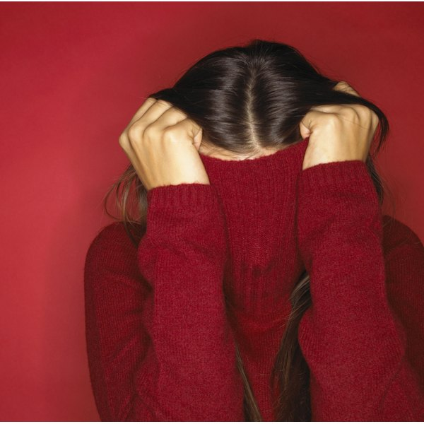 A woman hides as she pulls up the neck of her red turtleneck sweater.