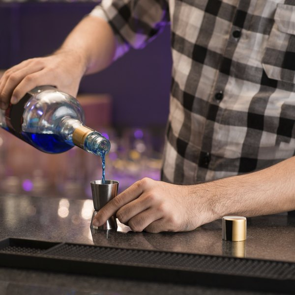 Close-up of a bartender pouring a shot of liquor.