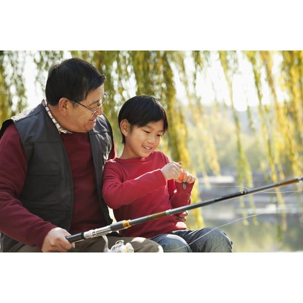A man and young boy are baiting their fishing rod.