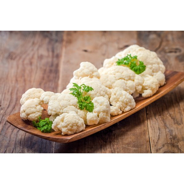 A wooden plate filled with raw cauliflower.
