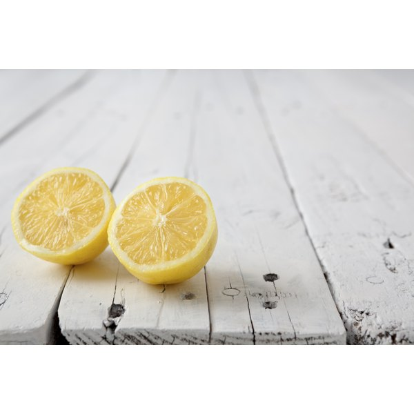 Two lemon halves on a wooden table.
