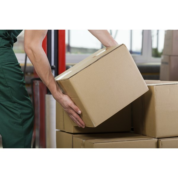 A close up of a man working in a warehouse lifing a box perhaps incorrectly.