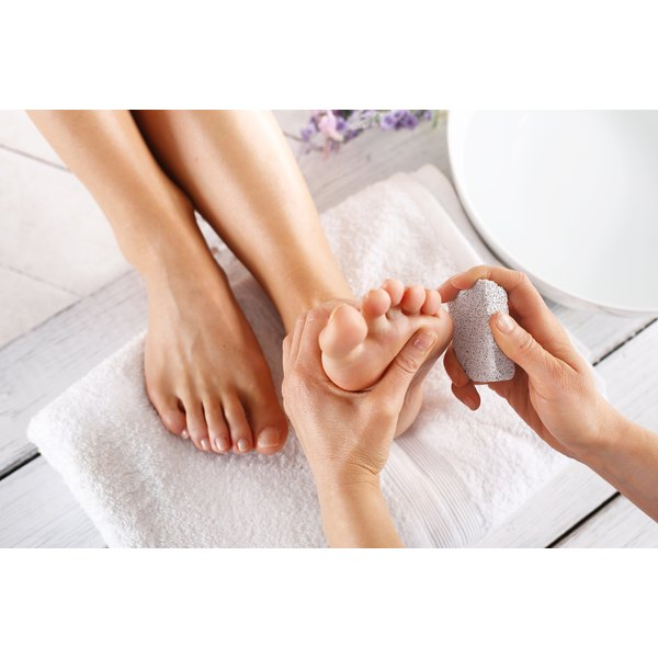 A close-up of an esthetican exfoliating a woman's foot with a pumice stone.