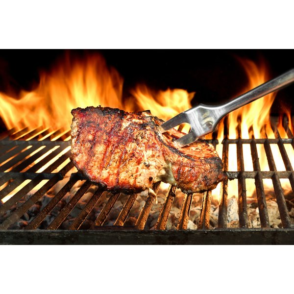 A fork is holding a piece of steak on the grill.