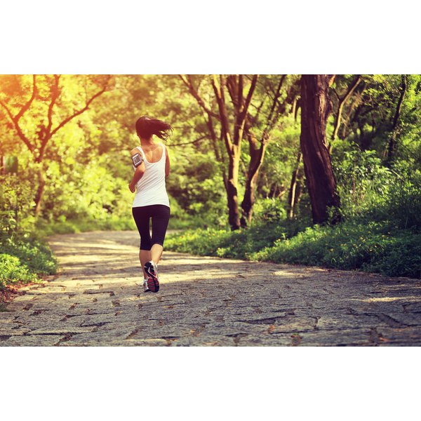 A woman is jogging on a trail.