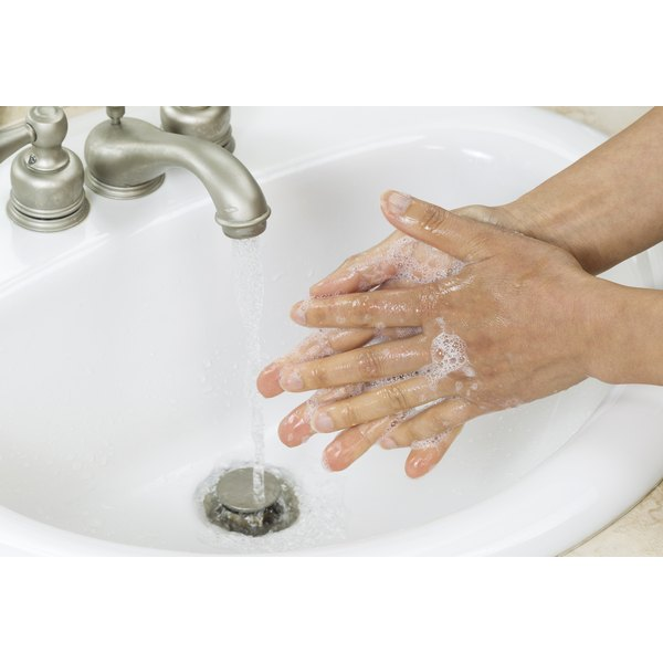 Close-up of a man washing his hands with soap and water.