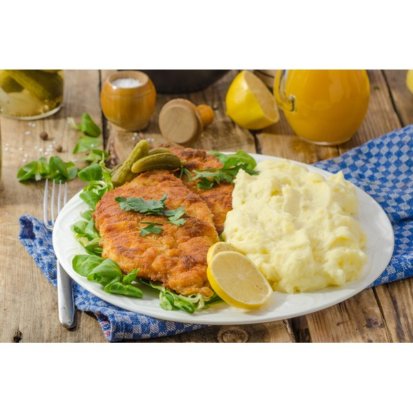 Veal cutlet on a plate with mashed potatoes.