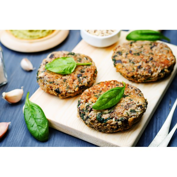 Vegetarian patties made with quinoa, eggplant, kale and chick peas on a board with garlic and basil.