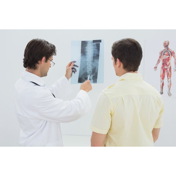 A doctor shows a patient his spine x-ray.