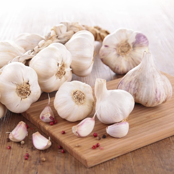 A large pile of garlic bulbs on a cutting board.