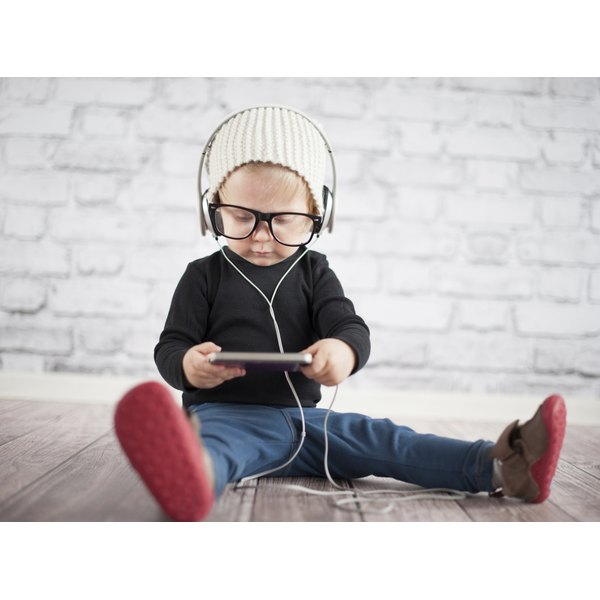 A toddler with headphones on listening to music off a digital device.