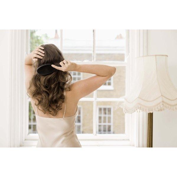 woman brushing hair in bedroom