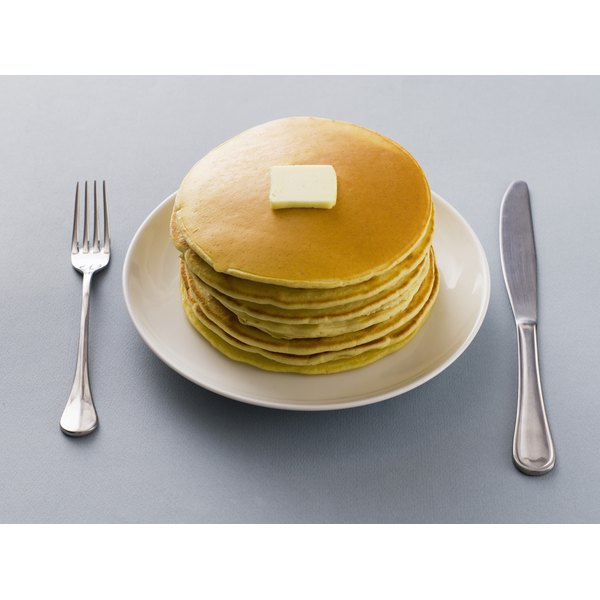 A stack of pancakes with a knife and fork.