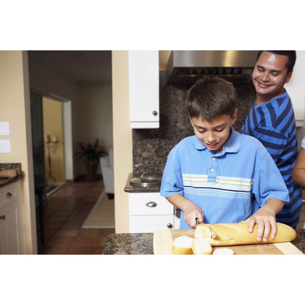 A young boy is slicing bread in the kitchen.