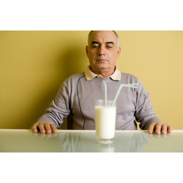 Glass of milk on table in front of man