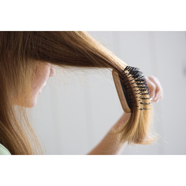 Close-up of a young woman brushing her hair.