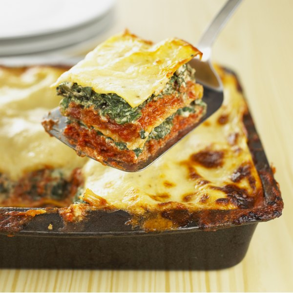 spatula with piece of vegetable lasagna over the homemade lasagna dish it was cut from