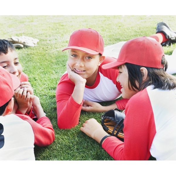 A group of children on a sports field dressed in baseball uniforms.