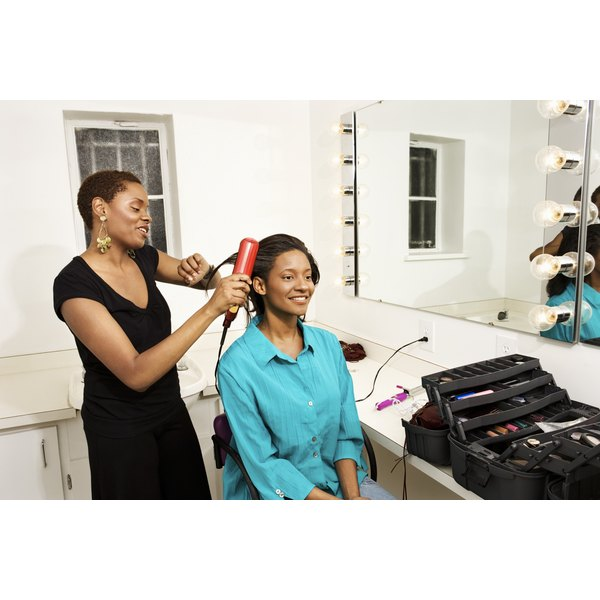 A hair stylist combing a woman of African descent's hair.