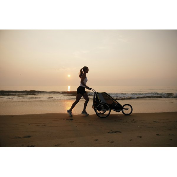 Young woman jogging with a stroller on the beach.