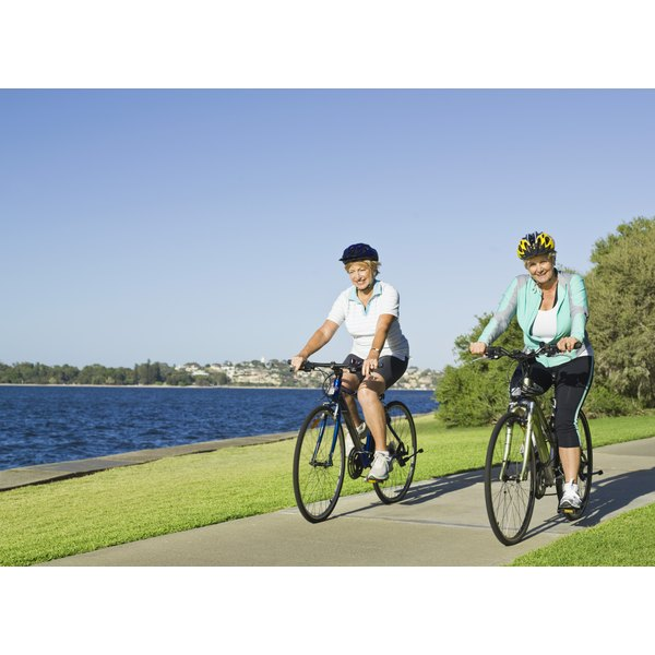 Two women riding bikes outdoors for exercise.